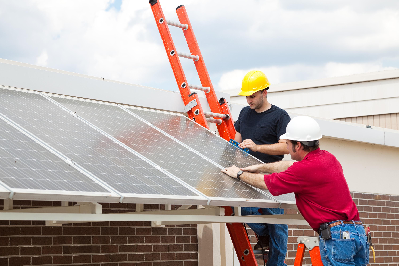 Bauarbeiten an Solaranlage mit zwei Arbeitern