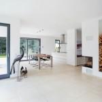 Helles Wohnzimmer mit Ofen und Brennholz